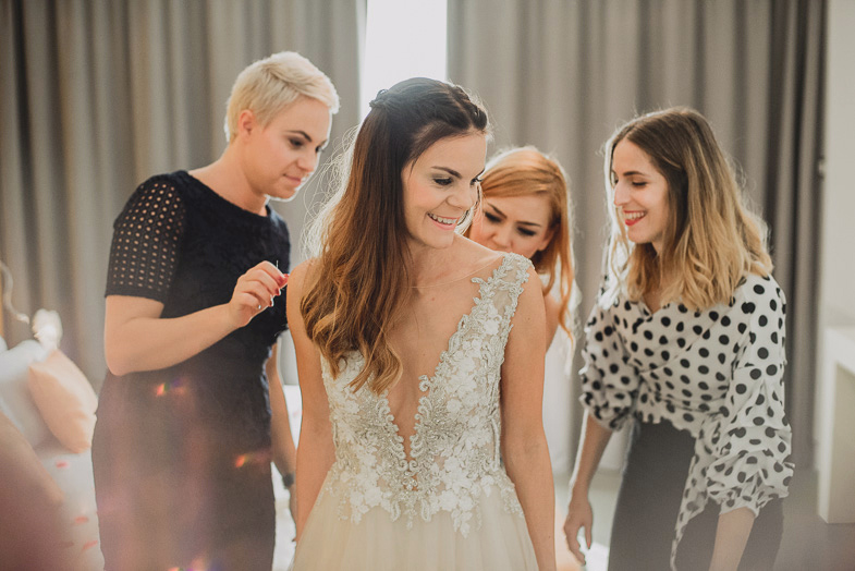 Prijateljice med zapenjanjem nevestine poročne obleke.