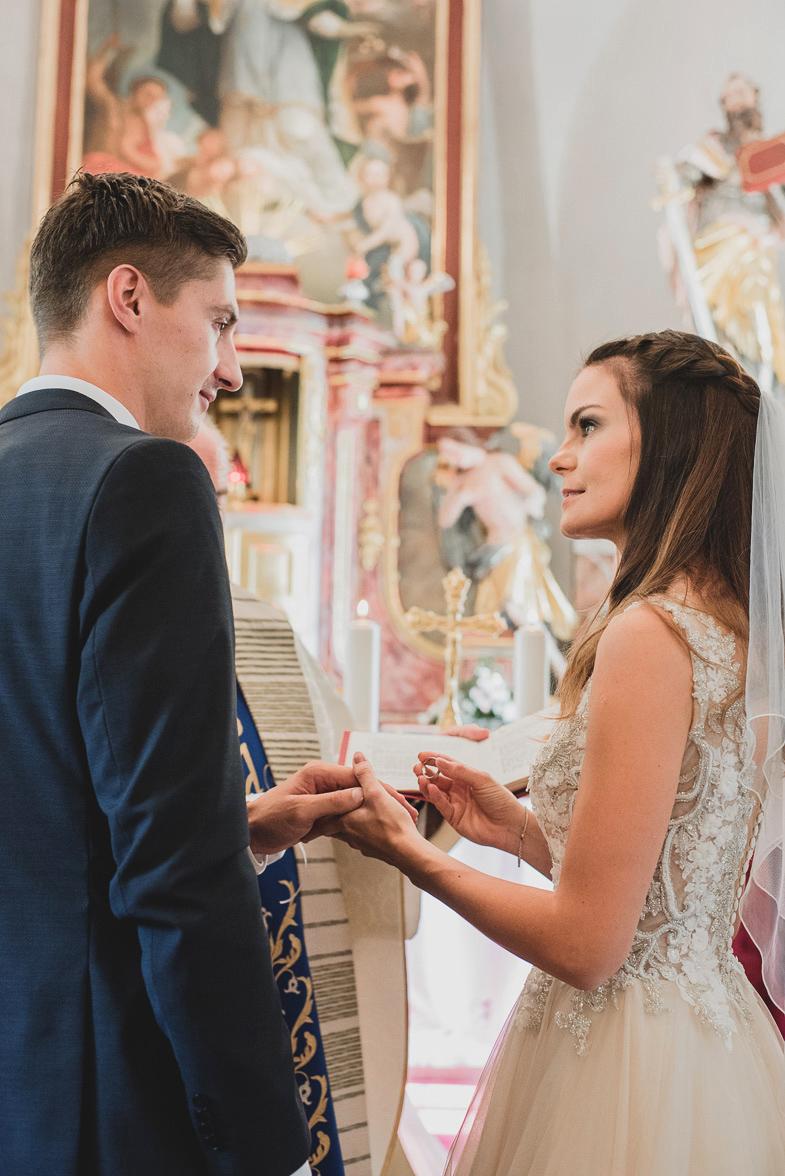 Mladoporočenca med izmenjavo poročnih prstanov.
