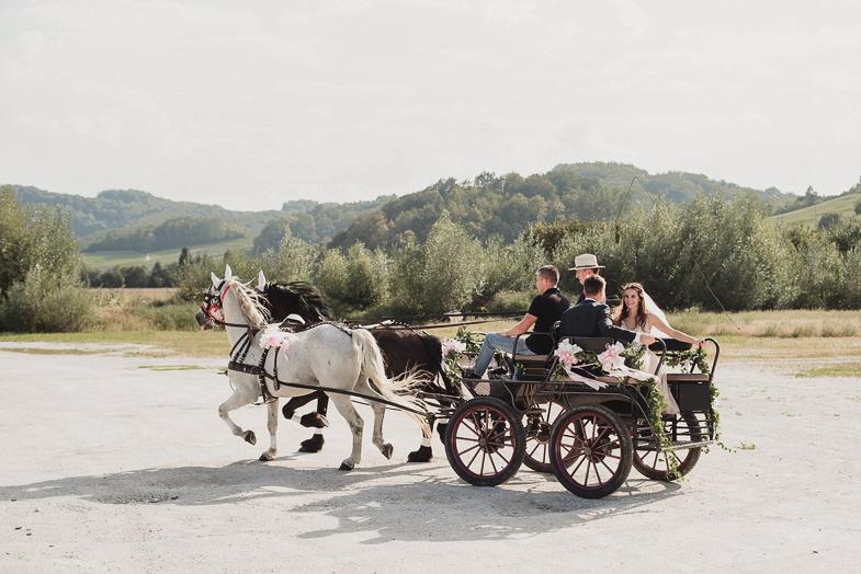 Ženin in nevesta v kočiji s konji.