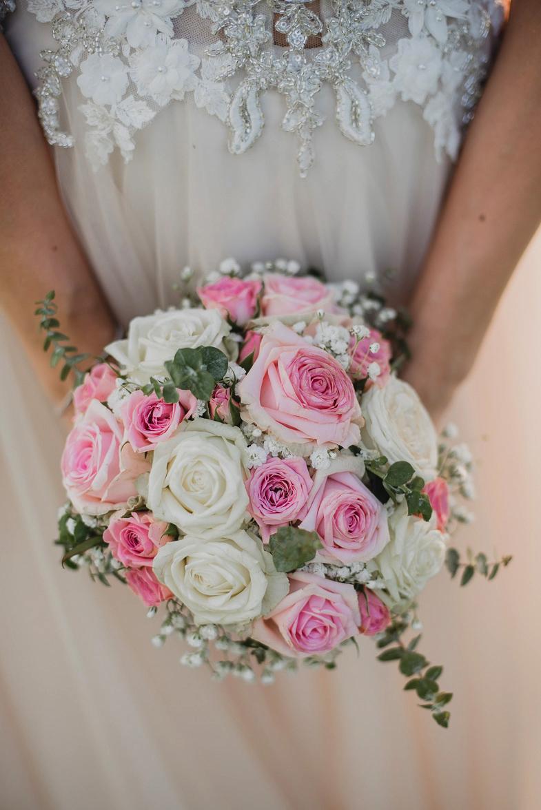 Fotografija belo roznega poročnega šopka.