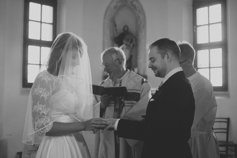 A bride and groom during an exchange of wedding vows with rings.