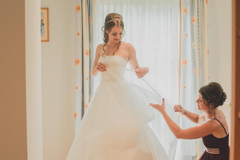 A bride dressing a white wedding dress.