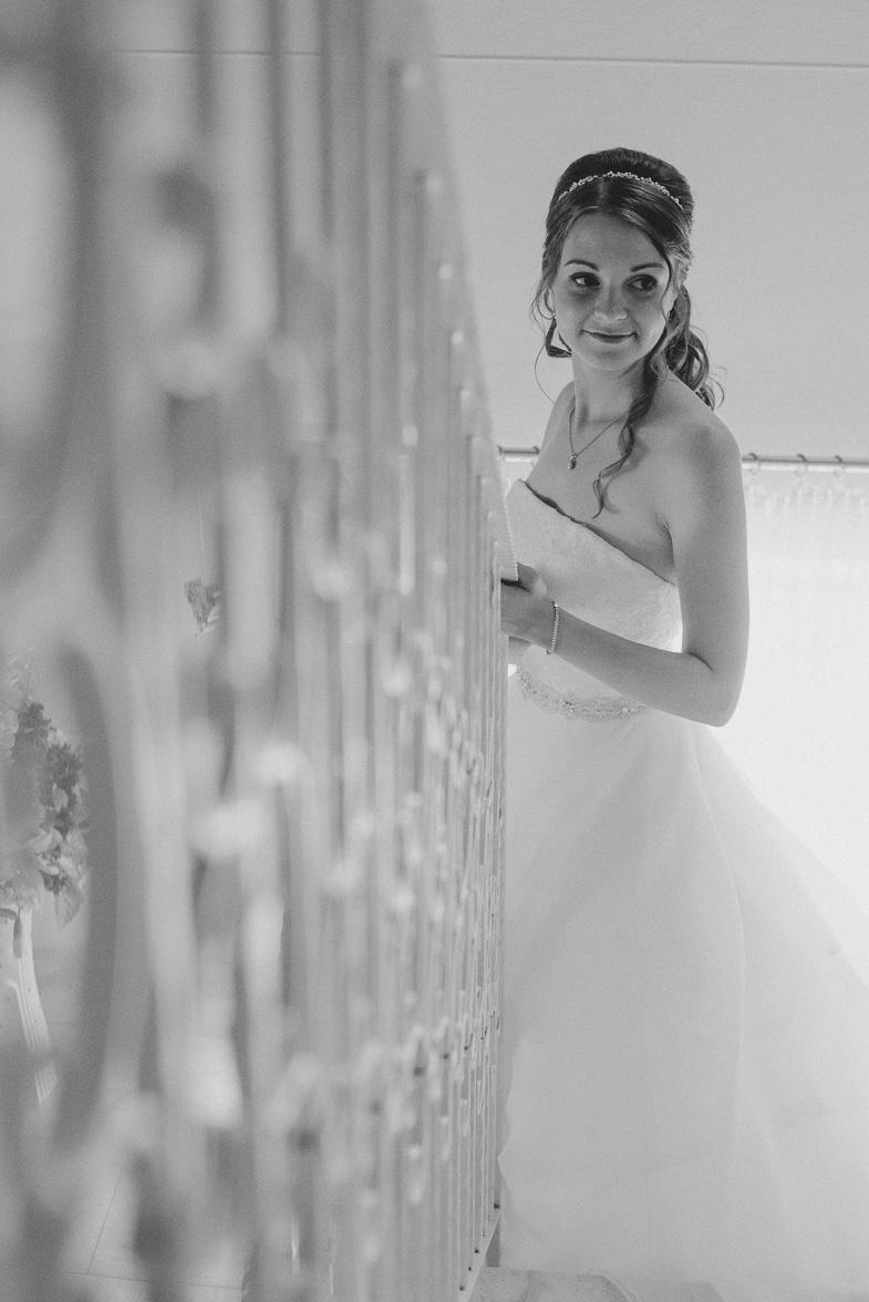Fotografija neveste v beli poročni obleki.