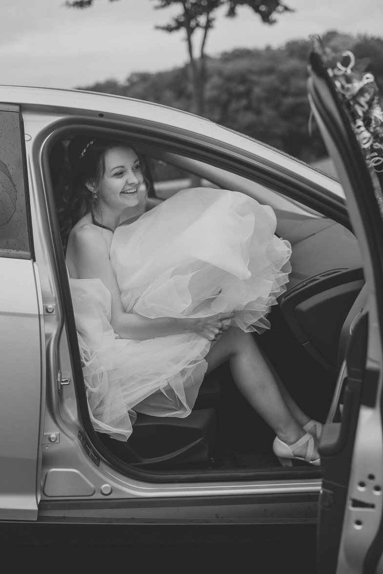 Bride while stepping into a wedding car.