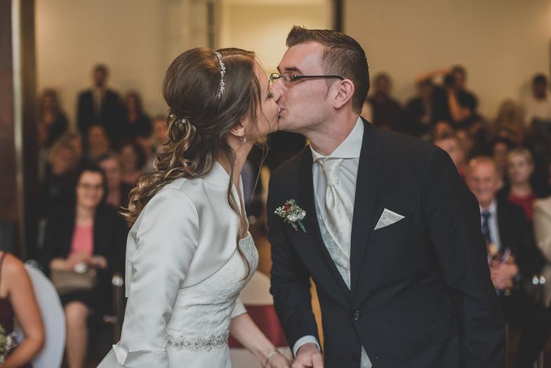A woman kissing a bride.