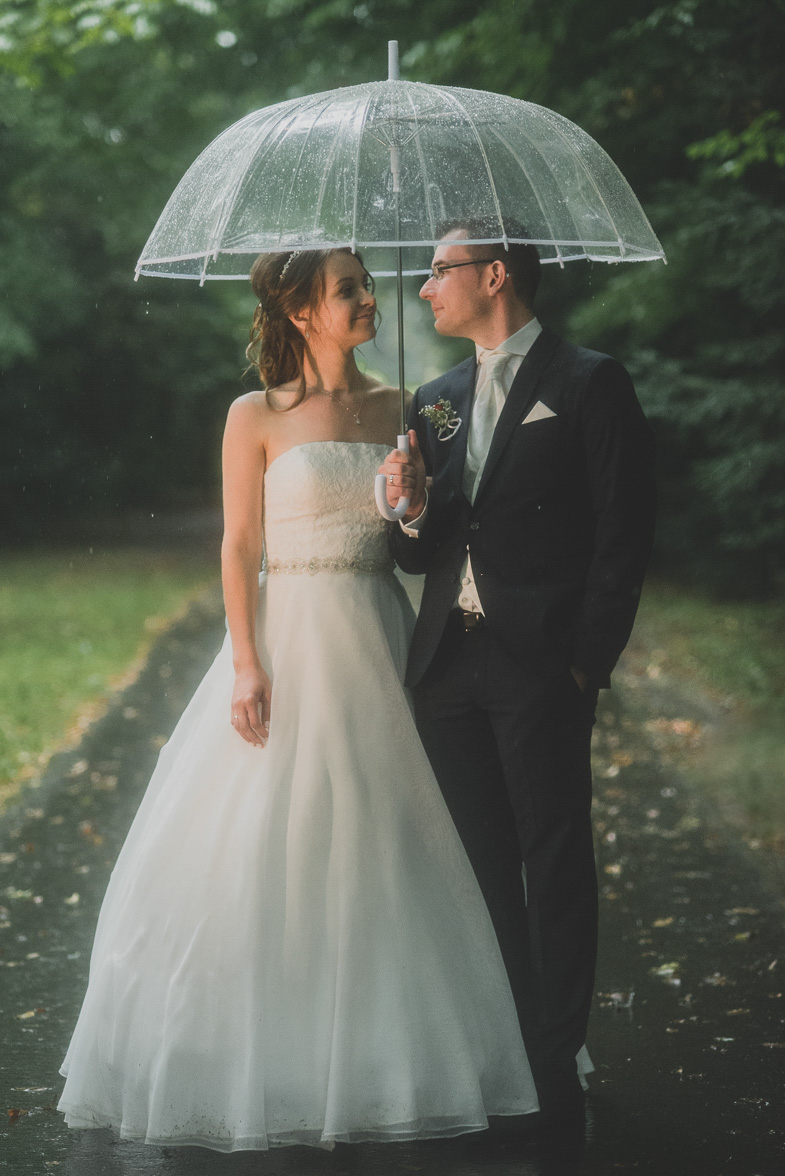 Portrait of newlyweds with umbrella on their rainy wedding day.