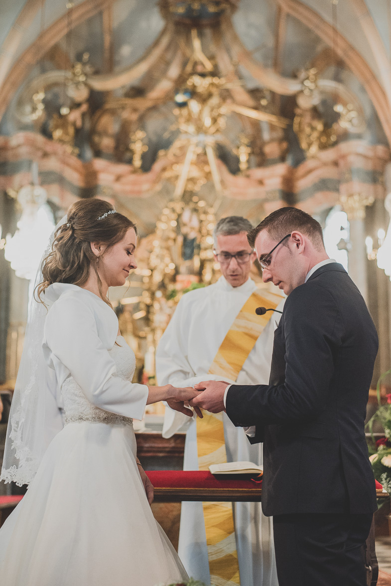 Newlyweds and a priest in front of the church altar.