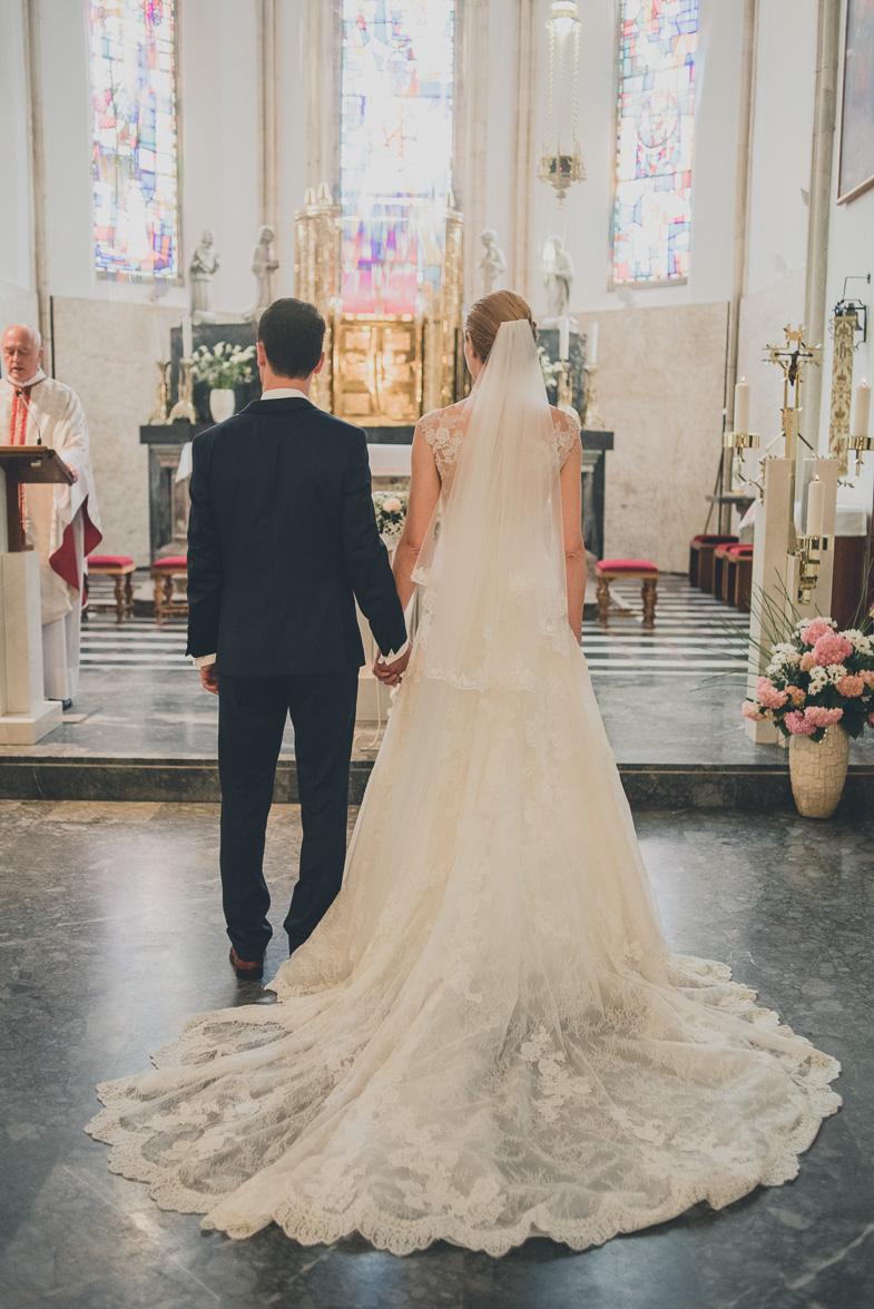 Nevesta oblečena v čipkasto poročno obleko s čipko.