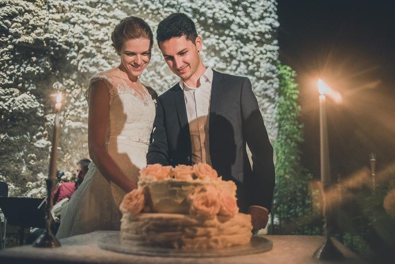 Mladoporočenca med razrezom poročne torte.