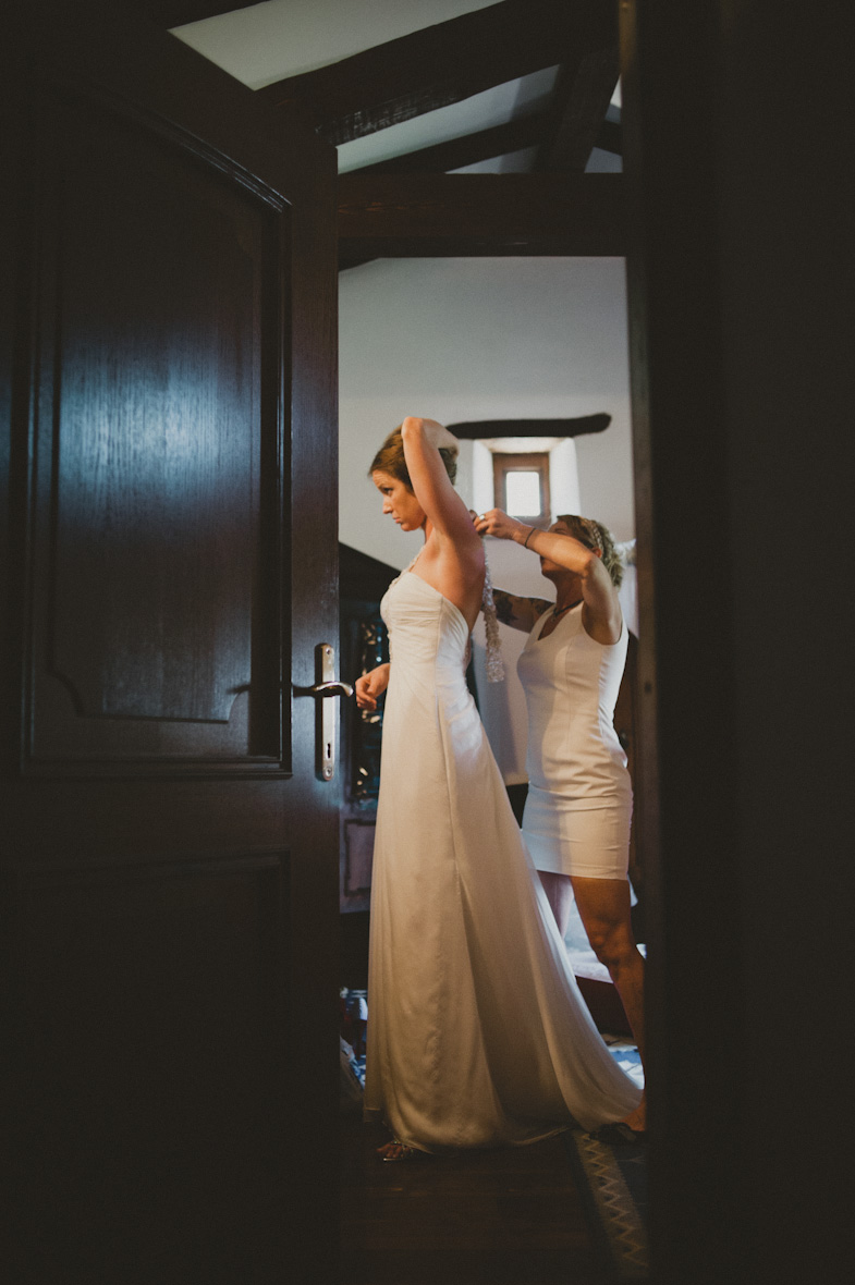 Bride during dressing a wedding dress.