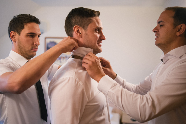 Zavezovanje kravate ženinu med poročnimi pripravami.