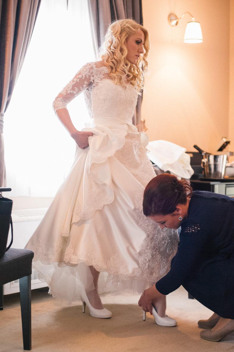 Nevesta med obuvanjem belih poročnih čevljev.