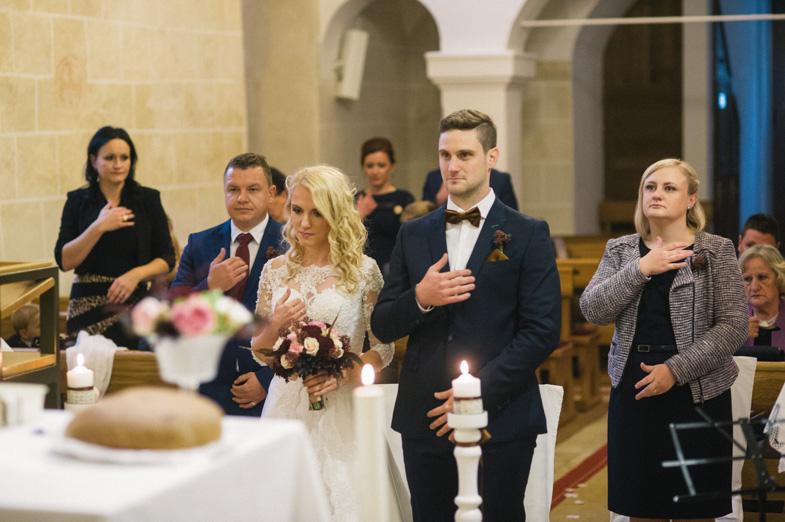 Portret neveste in ženina s pričama pred oltarjem.