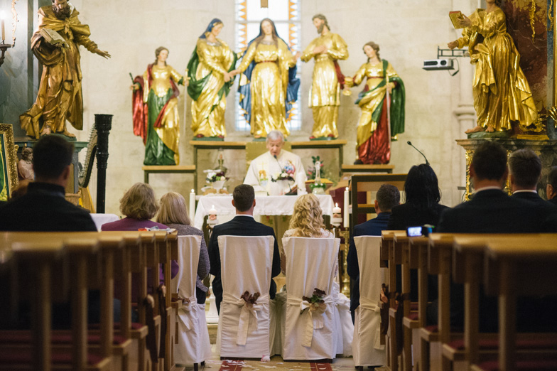Fotografija ženina in neveste, ki vstopata v sveti zakon.