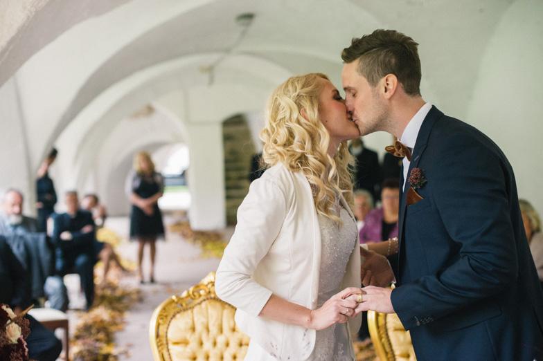Fotografija poročnega poljuba mladoporočencev.