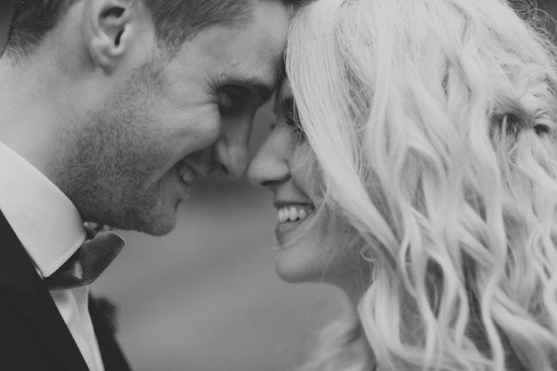 Poročna fotografija ženina in neveste, ki si izkazujeta ljubezen.