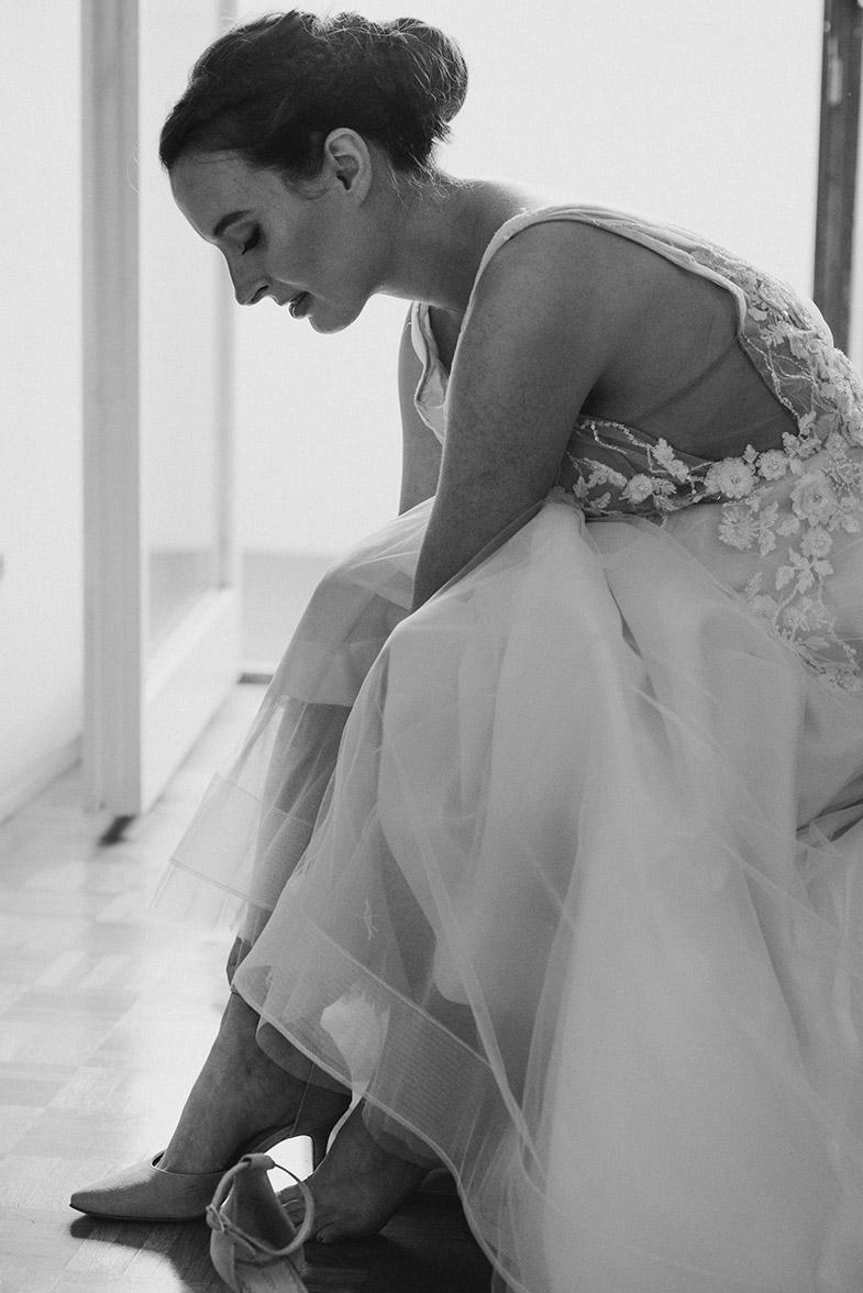 Nevesta med obuvanjem poročnih čevljev.