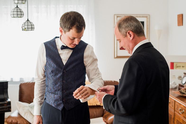 Ženin med oblačenjem poročne obleke.