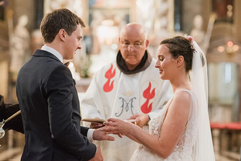Mladoporočenca in duhovnik med crkvenim poročnim obredom.