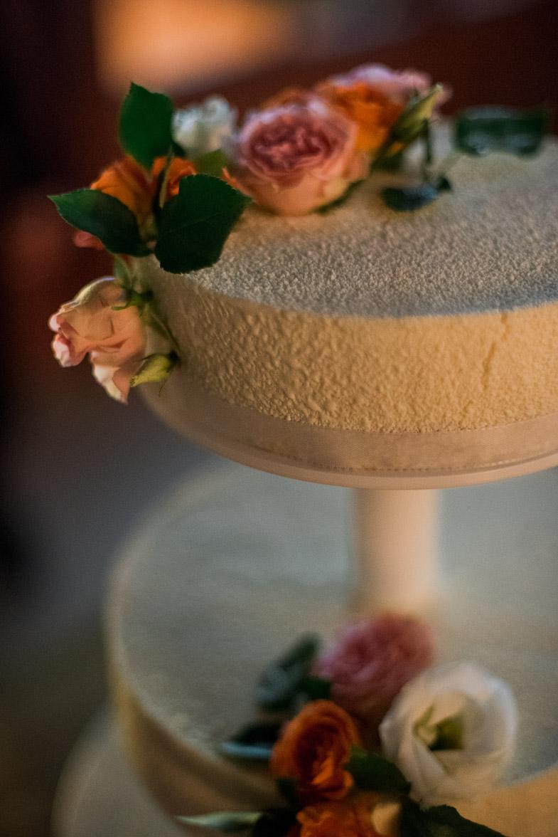 Slika poročne torte s svežim cvetjem.