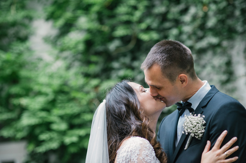 A portrait of a bride and groom with a breast bouquet.