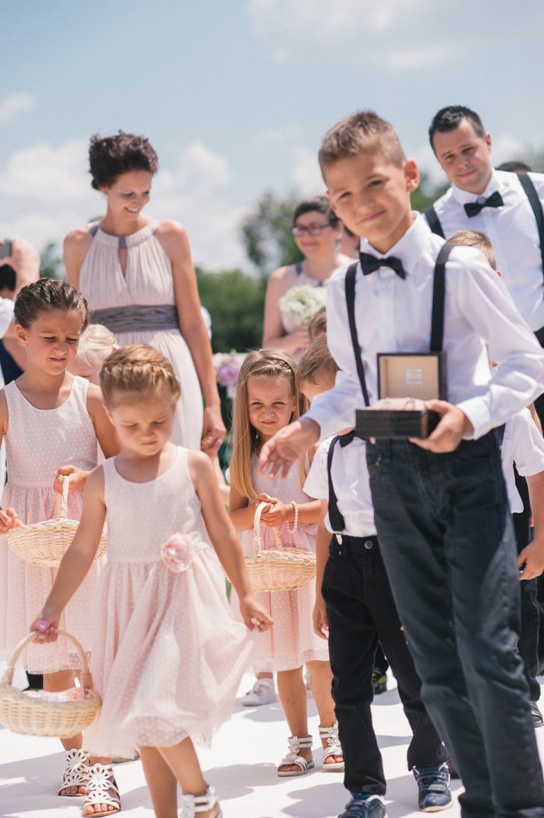 Deklice s cvetjem in deček s poročnimi prstani.