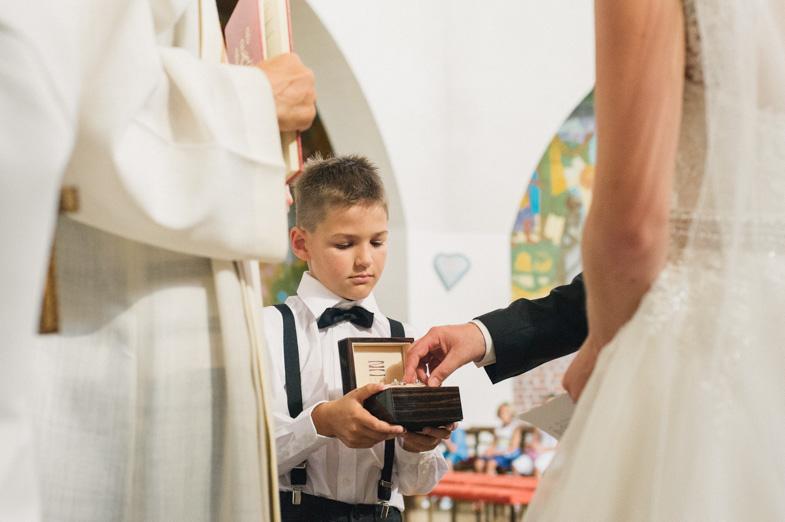 Fotografija dečka, ki drži blazinico s poročnimi prstani.