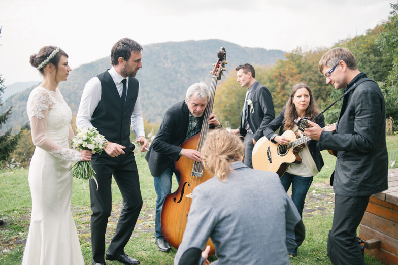 A bride and groom together with a wedding band in nature.