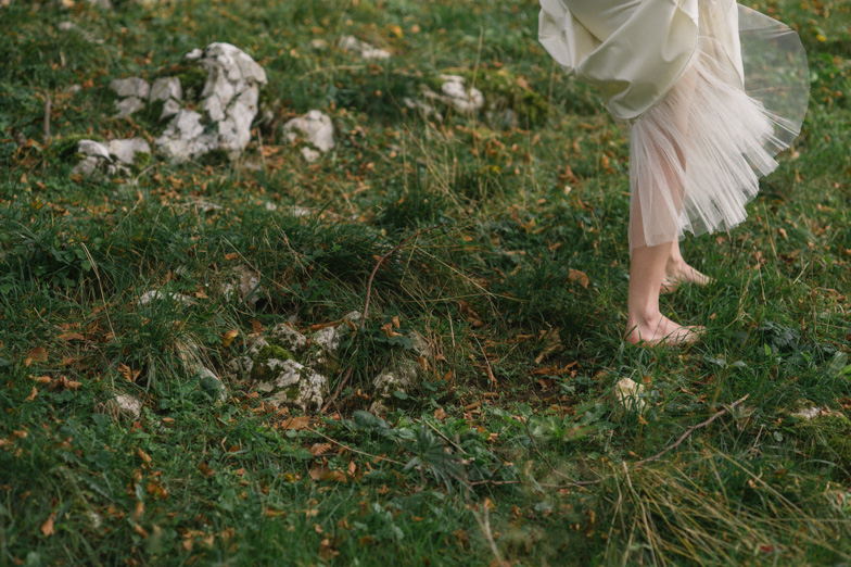 Fotografija neveste v stilu boho med hojo po travi.