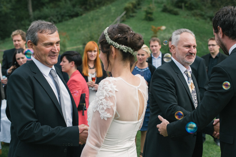 Newlyweds while receiving congratulations from wedding guests.