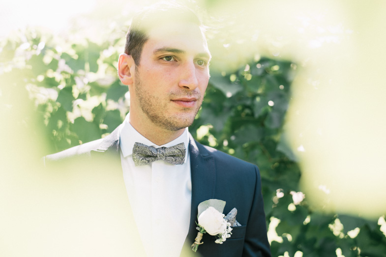 Portrait of a groom with a bouquet.