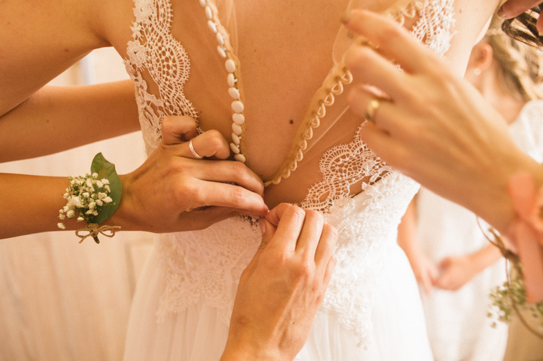 A bridesmaid assistant while closing a wedding dress.