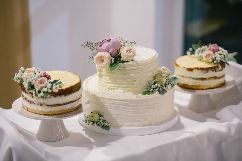 Photo of a wedding cake with fresh flowers.