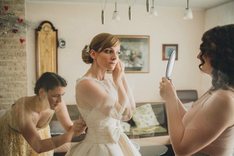 Nevesta med pripenjanjem poročnih modnih dodatkov.