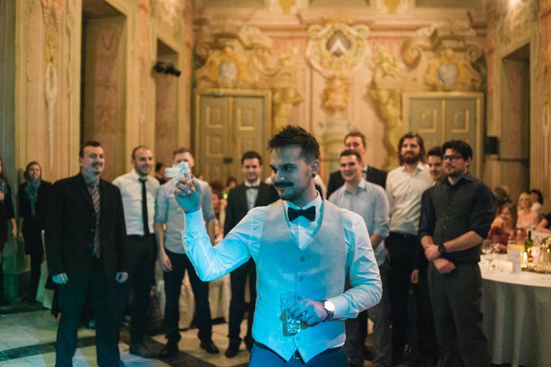 A photograph of a groom throwing a garter at wedding.