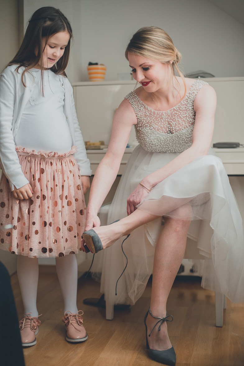 Bride while putting high-heeled wedding shoes.
