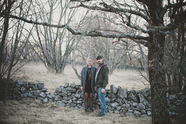 A photo of a couple standing in front of a wall.